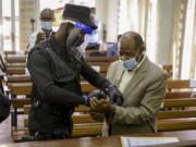 """A policeman handcuffs Paul Rusesabagina, right, whose story inspired the film """"Hotel Rwanda"""", before leading him out of the Kicukiro Primary Court in the capital Kigali, Rwanda Monday, Sept. 14, 2020. A Rwandan court on Monday charged Paul Rusesabagina with terrorism, complicity in murder, and forming an armed rebel group, while Rusesabagina declined to respond to all 13 charges, saying some did not qualify as criminal offenses and saying that he denied the accusations when he was questioned by Rwandan investigators."""