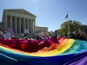 FILE - In this April 28, 2015 file photo, demonstrators stand in front of a rainbow flag of the Supreme Court in Washington. In 2019, there were slightly less than 1 million same-sex couple households in the U.S., and a majority of those couples were married. New figures released Thursday, Sept. 17, 2020 by the U.S. Census Bureau shows that of the 980,000 same-sex couple households, 58% were married couples and 42% were unmarried partners.
