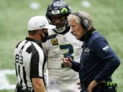 Seattle Seahawks quarterback Russell Wilson (3) and Seattle Seahawks head coach Pete Carroll speak to back judge ShawnA  Hochuli (83) during the first half of an NFL football game against the Atlanta Falcons, Sunday, Sept. 13, 2020, in Atlanta.