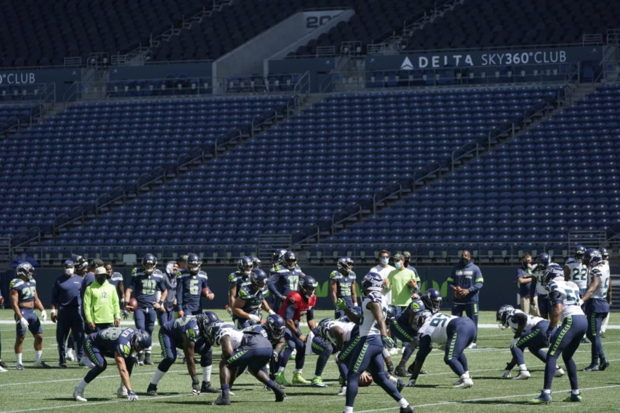 Seattle Seahawks quarterback Russell Wilson, center, waits for the snap during warmups in front of empty seats at CenturyLink Field before an NFL football mock game, Wednesday, Aug. 26, 2020, in Seattle. (AP Photo/Ted S.