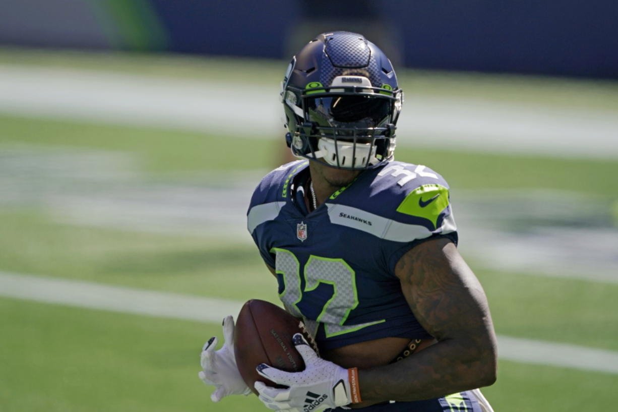 Seattle Seahawks running back Chris Carson holds the football as players warm up for an NFL football scrimmage Wednesday, Aug. 26, 2020, in Seattle. (AP Photo/Ted S.