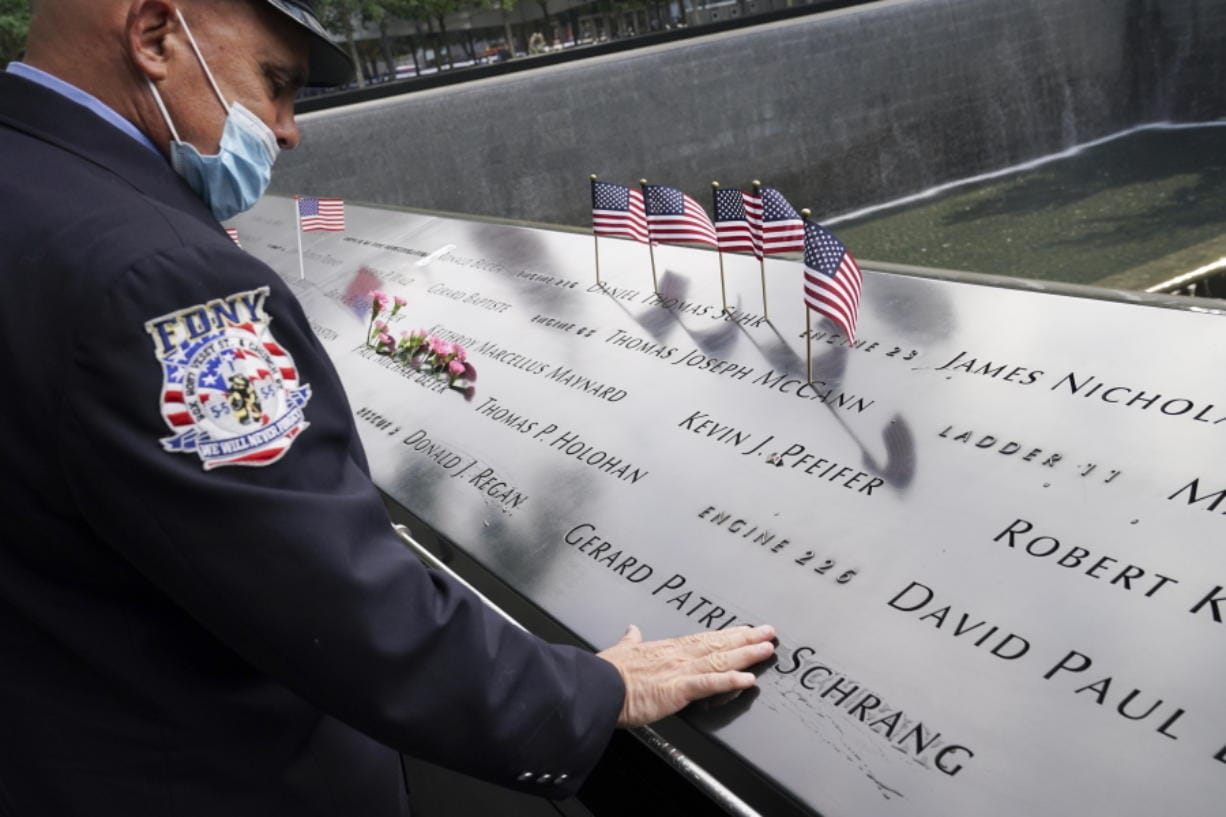 A mourner brushes water with his fingers over the name cut-outs of the deceased at the National September 11 Memorial and Museum, Friday, Sept. 11, 2020, in New York.