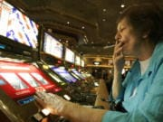 FILE - In this Dec. 28, 2005, file photo, Judy King of Daytona Beach, Fla., holds her cigarette while playing a slot machine at the MGM Grand hotel-casino in Las Vegas. One of the last Las Vegas Strip resorts to reopen after coronavirus closures will be the first to be smoke-free, MGM Resorts International announced Monday, Sept. 14, 2020. Park MGM will prohibit tobacco smoke inside when it opens Sept. 30, said Anton Nikodemus, president and chief operating officer of the 3,000-room property that many remember as the Monte Carlo casino-hotel. (AP Photo/Jae C.