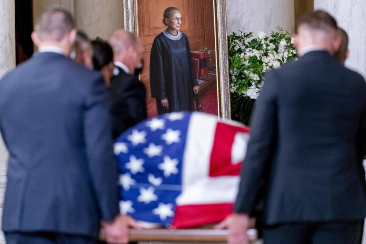 The flag-draped casket of Justice Ruth Bader Ginsburg, carried by Supreme Court police officers, arrives in the Great Hall at the Supreme Court in Washington, Wednesday, Sept. 23, 2020. Ginsburg, 87, died of cancer on Sept. 18.