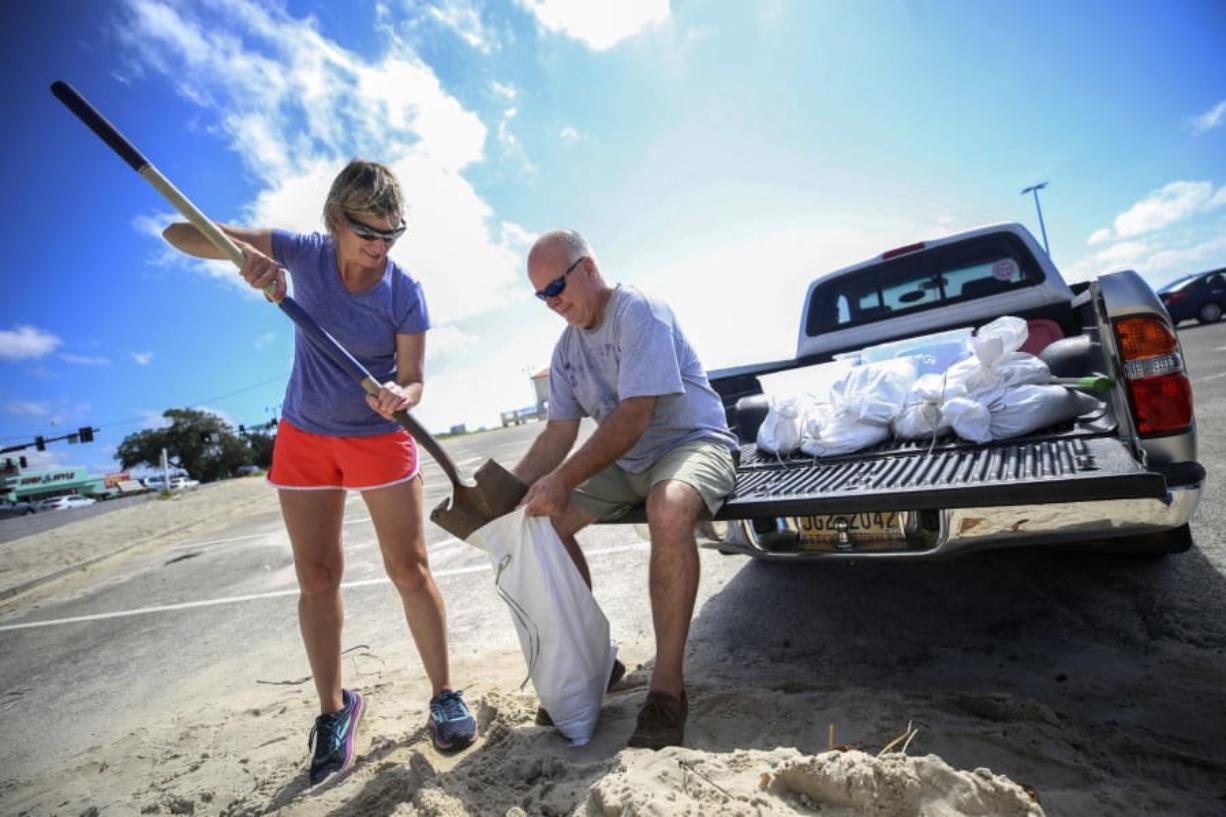 Kim Miller and Monty Graham open their truck bed and began loading up sandbags along U.S. 90  in preparation for Tropical Storm Sally, Sunday, Sept. 13, 2020 in Gulfport, Miss.