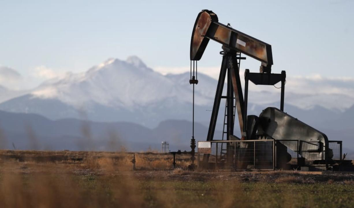 FILE - This Dec. 22, 2018, file photo shows a pump jack over an oil well along Interstate 25 near Dacono, Colo. Federal courts have delivered a string of rebukes to the Trump administration over what they found were failures to protect the environment and address climate change as it promotes fossil fuel interests and the extraction of natural resources from public lands.