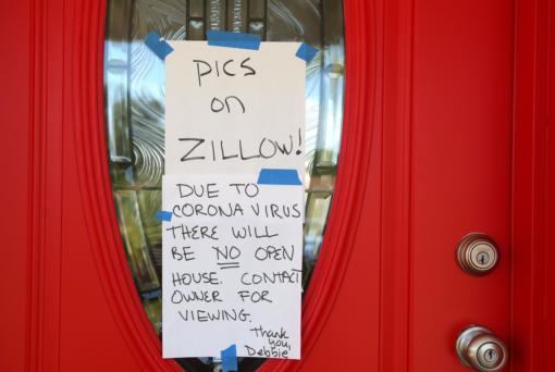 A sign on the front door of a home for sale in St. Petersburg, on March 23, 2020, that tells potential buyers that photos of the home are on Zillow.