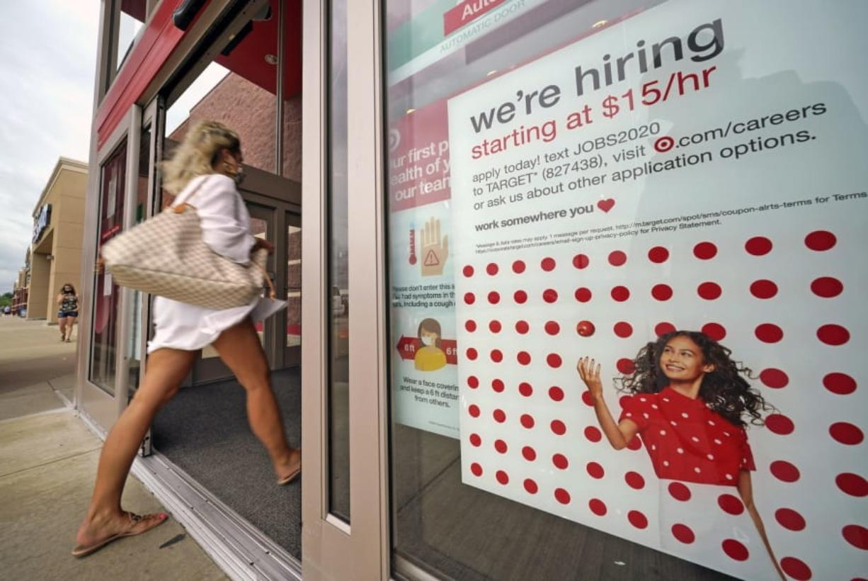 FILE - In this Sept. 2, 2020, file photo, a help wanted sign hangs on the door of a Target store in Uniontown, Pa. Hundreds of thousands of Americans likely applied for unemployment benefits last week, a high level of job insecurity that reflects economic damage from the coronavirus outbreak. Economists expect that 850,000 people sought jobless aid, down from 884,000 the week before, according to a survey by the data firm FactSet. (AP Photo/Gene J.