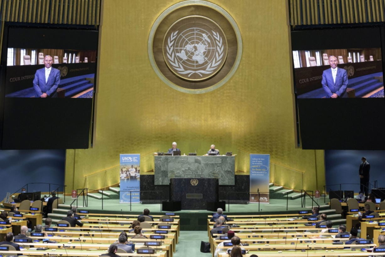 In this photo provided by the United Nations, President of the International Court of Justice, Judge Abdulqawi Ahmed Yusuf, is seen on screens as he addresses the United Nations General Assembly to commemorate the 75th anniversary of the United Nations.