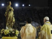 FILE - In this Nov. 21, 2019 file photo, Pope Francis blesses a statue of the Mother Mary as he celebrates Mass at the National Stadium, in Bangkok, Thailand. Pope Francis is giving his blessing to a new Vatican think tank that is seeking to prevent the Mafia and organized crime groups from exploiting the image of the Virgin Mary for their own illicit ends.