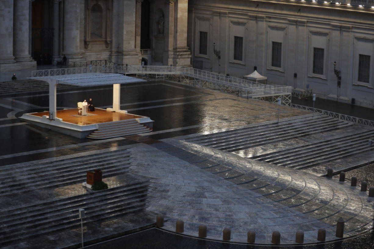 FILE - In this photo taken on March 27, 2020, Pope Francis, white figure standing alone at center, delivers an Urbi et orbi prayer from the empty St. Peter's Square, at the Vatican. If ever there was a defining moment of Pope Francis during the coronavirus pandemic, it came on March 27, the day Italy recorded its single biggest daily jump in fatalities. From the rain-slicked promenade of St. Peter's Basilica, Francis said the virus had shown that we're all in this together, that we need each other and need to reassess our priorities.