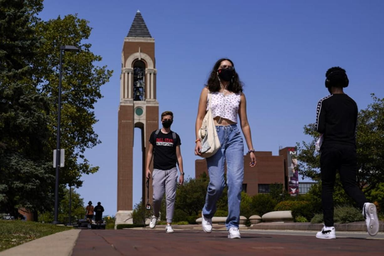 Masked students walk through the campus of Ball State University in Muncie, Ind., Thursday, Sept. 10, 2020. College towns across the U.S. have emerged as coronavirus hot spots in recent weeks as schools struggle to contain the virus. Out of nearly 600 students tested for the virus at Ball State, more than half have returned been found positive, according to data reported by the school. Dozens of infections have been blamed on off-campus parties, prompting university officials to admonish students.