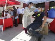 FILE - In this Aug. 6, 2020, file photo, Hialeah Fire Department Firefighter-Paramedic Laura Nemoga, right, winces as medical assistant Jesus Vera performs a COVID-19 test at Hialeah Fire Station #1, in Hialeah, Fla. The torrid coronavirus summer across the Sun Belt is easing after two disastrous months that brought more than 35,000 deaths.