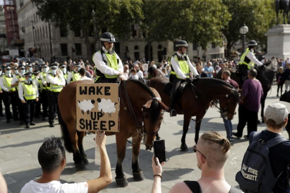 """A protester holds up a placard in front of police officers during a """"Resist and Act for Freedom"""" protest against a mandatory coronavirus vaccine, wearing masks, social distancing and a second lockdown, in Trafalgar Square, London, Saturday, Sept. 19, 2020."""