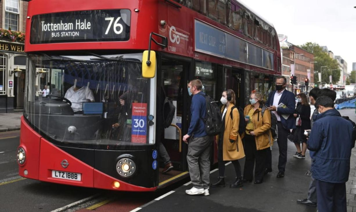 People board a bus outside Waterloo station in London, Wednesday, Sept. 23, 2020, after Prime Minister Boris Johnson announced a range of new restrictions to combat the rise in coronavirus cases in England, Wednesday, Sept. 23, 2020.
