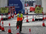 A staff member waits at empty lanes of a Covid-19 drive thru testing facility at Twickenham stadium in London, Thursday, Sept. 17, 2020. Britain has imposed tougher restrictions on people and businesses in parts of northeastern England on Thursday as the nation attempts to stem the spread of COVID-19, although some testing facilities remain under-utilised.