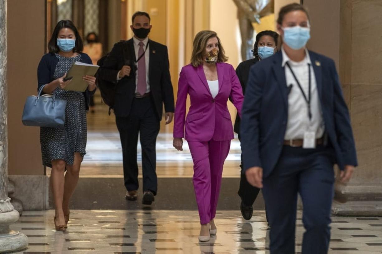 House Speaker Nancy Pelosi of Calif., center, walks to her office, Monday, Sept. 14, 2020, on Capitol Hill in Washington.