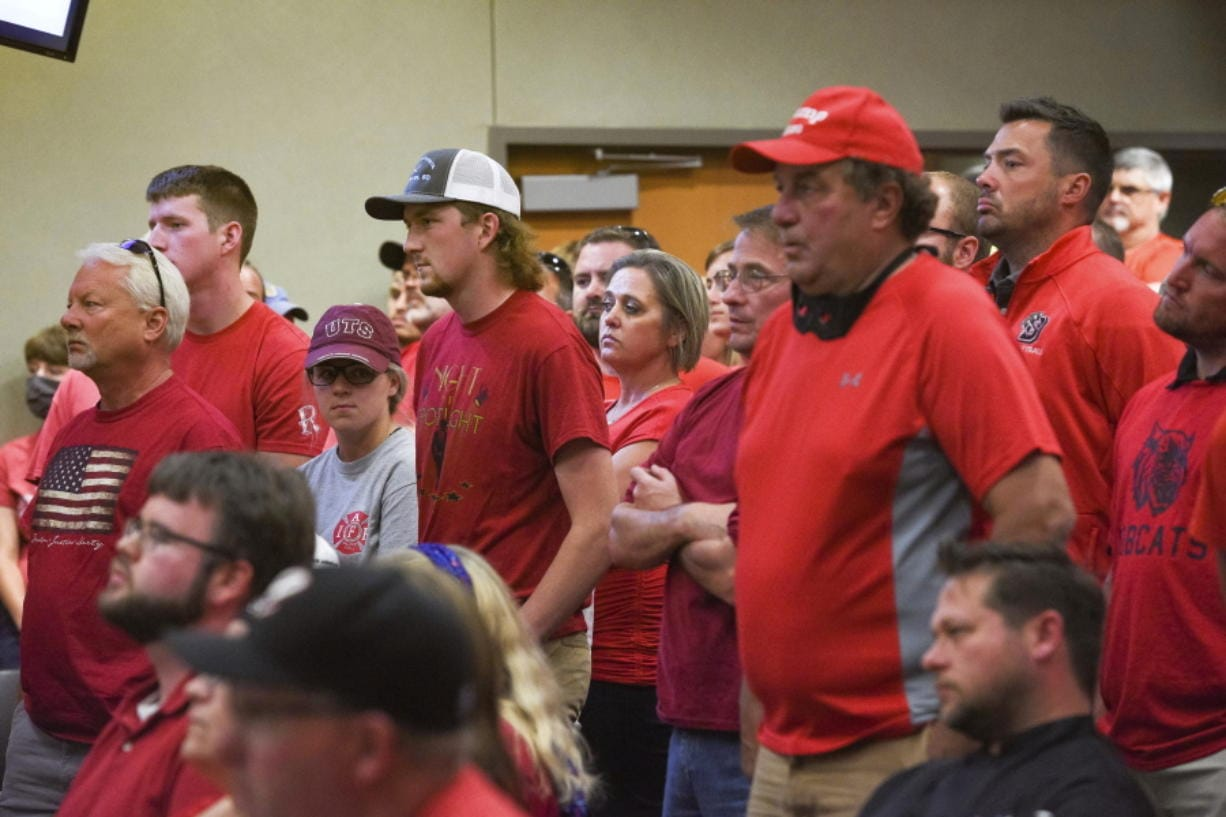 People wear red in solidarity against a potential city-wide mask mandate during a city council meeting on Wednesday, Sept. 2, 2020, in Brookings, S.D. Coronavirus infections in the Dakotas are growing faster than anywhere else in the nation, fueling impassioned debates over masks, personal responsibility and freedom after months in which the two states avoided the worst of the pandemic.