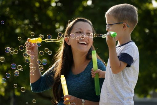Claire Reagan plays with her son Evan, 5, Monday, Sept. 21, 2020, outside her home in Olathe, Kan. Reagan is keeping her son from starting kindergarten and her daughter Abbie, 3, from preschool due to concerns about the coronavirus pandemic.