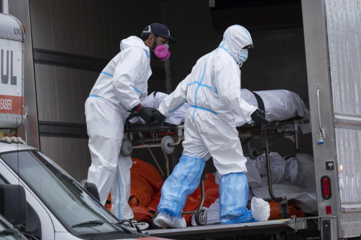 FILE - In this April 29, 2020, file photo, workers move bodies to a refrigerated truck from the Andrew T. Cleckley Funeral Home in the Brooklyn borough of New York. During the deadliest days of the coronavirus outbreak in New York City, the bodies piled up at the funeral home -- and the stench that came with it -- at an alarming rate. Cleckley says what happened next made him the scapegoat for an unforeseen crisis -- hundreds of COVID-19 deaths a day in New York that overwhelmed funeral homes across the city. Authorities swept in and suspended his license in an episode that made headlines in a city already reeling from other horrors of the pandemic.