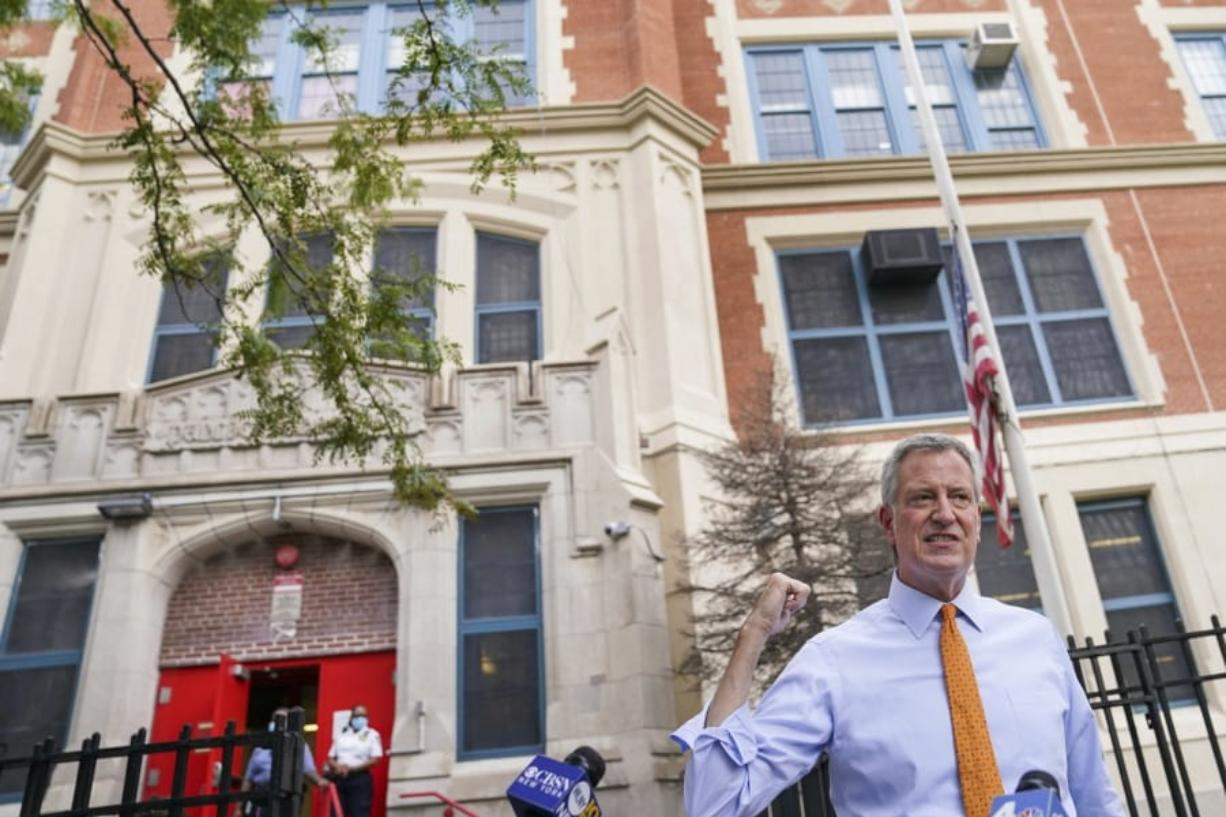 FILE - In this Aug. 19, 2020, file photo, New York Mayor Bill de Blasio speaks to reporters after visiting New Bridges Elementary School to observe pandemic-related safety procedures, in the Brooklyn borough of New York. For most schoolchildren in New York City, Monday, Sept. 21, 2020, will mean back to school, but not back to the classroom. Only pre-kindergarteners and some special education students are scheduled to end a six-month absence from school buildings.