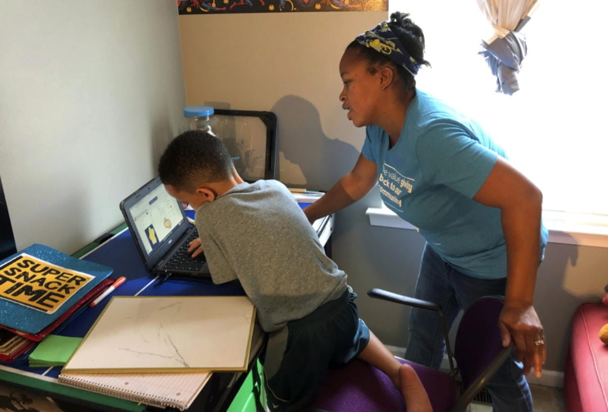 Tiffany Shelton helps her 7-year-old son, P.J. Shelton, a second-grader, during an online class at their home in Norristown, Pa., on Thursday, Sept. 3, 2020. Norristown Area School District plans to offer online-only instruction through at least January 2021.