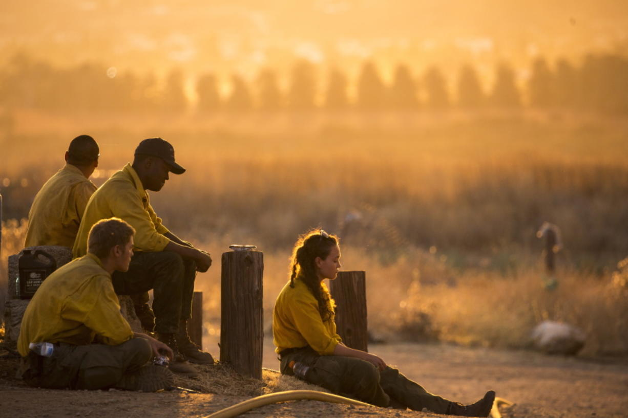 Firefighters rest during a wildfire in Yucaipa, Calif., Saturday, Sept. 5, 2020. Firefighters trying to contain the massive wildfires in Oregon, California and Washington state are constantly on the verge of exhaustion as they try to save suburban houses, including some in their own neighborhoods. (AP Photo/Ringo H.W.