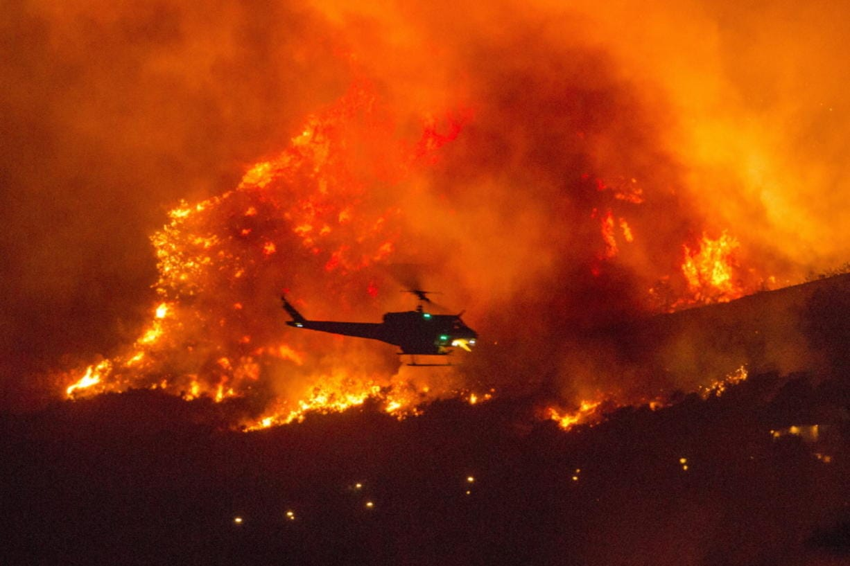 A helicopter prepares to drop water at a wildfire in Yucaipa, Calif., Saturday, Sept. 5, 2020. (AP Photo/Ringo H.W.