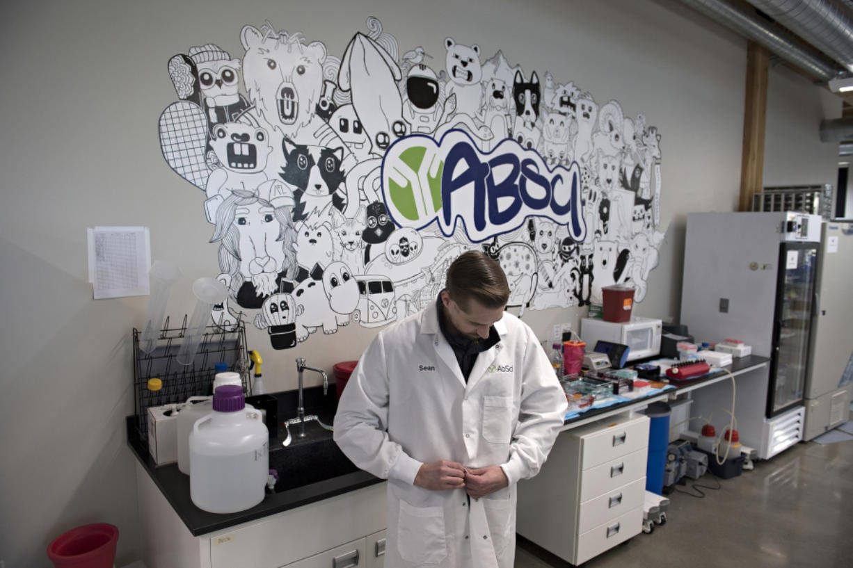 Sean McClain, founder and CEO of AbSci in downtown Vancouver, prepares his lab coat before pausing for a portrait in his company's lab. The company is preparing to start construction on a 60,000-square-foot building in Vancouver to house all operations and employees, according to McClain.