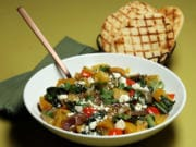 Grilled golden beets center a fall salad that makes a colorful dinner, with sauteed beet greens, red onions, bell pepper, herbs and crumbled feta.