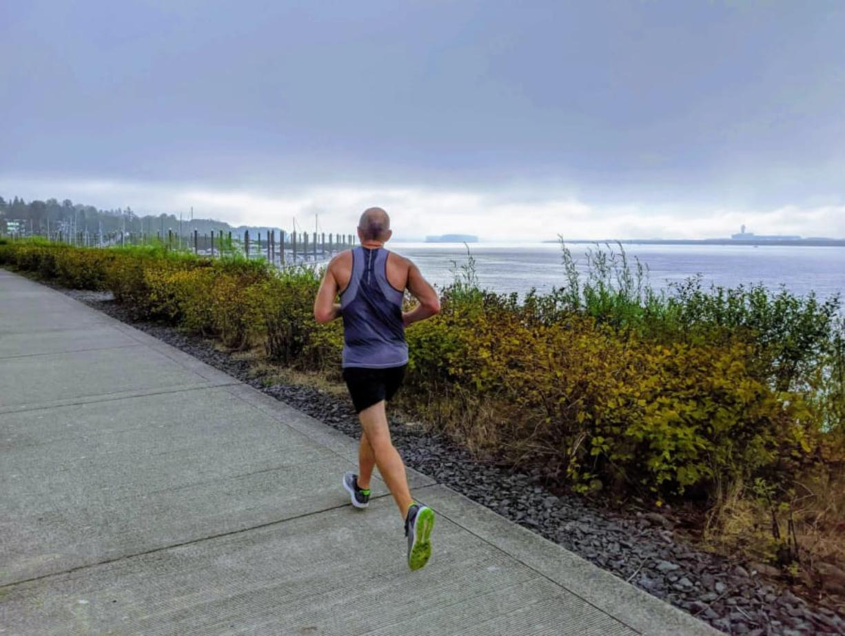 Rolf Vellek of Vancouver runs along the Columbia River on the marked course for the PeaceHealth Apple Tree Half Marathon last month.