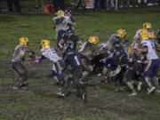 Columbia River and Hockinson play through muddy conditions late in the fourth quarter at Hockinson High School on Friday night, Oct. 14, 2016.