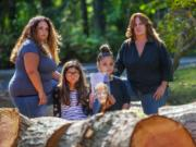 Tyffani Murillo, her daughters Rylie Dickinson, 9, and Emmie Dickinson, 12, with their grandmother Kareen Huffman are photographed near some freshly cut trees on Huffman's property in Lake Stevens. The young granddaughters are holding a photograph of their great grandma Darlene Mach who passed away earlier this year at the age of 83. The girls great-great grandmother, Kathleen Chappell died last year at the age of 103. Photographed on September 22, 2020.