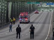 First responders keep an eye on the scene as police work on the Interstate Bridge as lanes are cleared of traffic on Tuesday morning, Oct. 20, 2020.
