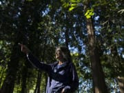 Elizabeth Koch of Vancouver, who is a cancer survivor, points out some of her favorite areas in Jorgenson Woods Neighborhood Park. Koch believes in the therapeutic power of nature and forests.