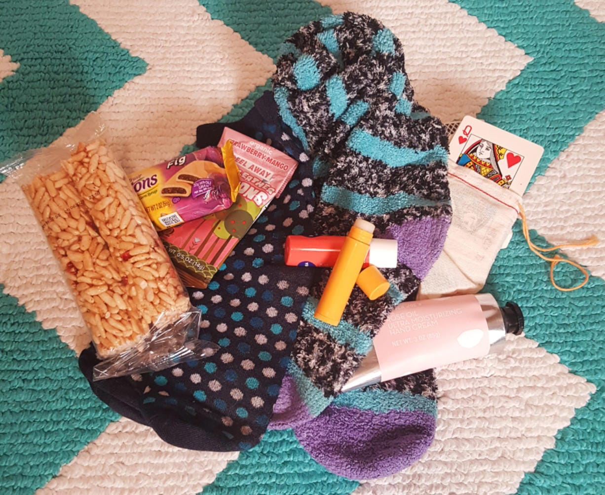 Just a few small things can make a big difference: snacks, warm socks, lip balm, lotion and a deck of cards can make the hours pass more easily.