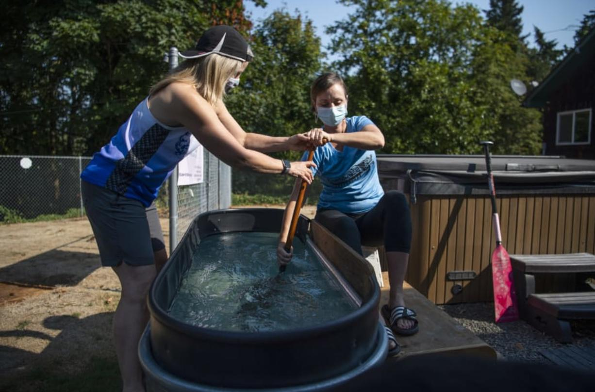 Laura Thornquist, left, demonstrates how she has been coaching teammates while the coronavirus pandemic has kept them off the lake. She corrects teammate Britten Witherspoon's form as she paddles in a water trough in Thornquist's Woodland backyard.