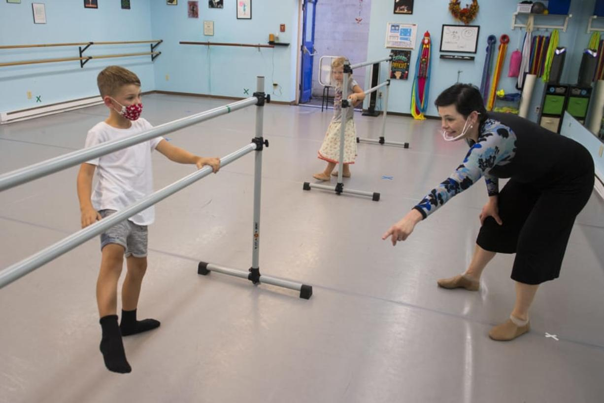 """Jeremiah Andryushin, 7, of Vancouver, from left, gets some help with his footwork while joined by his sister, Ada, 4, from dance instructor Liz Borromeo at Liz Borromeo Dance. Borromeo teaches small classes while others join in on Zoom, a platform she hopes to abandon when the pandemic is over. """"Zoom is great, I think, for lectures, but it's a challenging platform for dance,"""" she said. """"The day I get to delete my Zoom account will be a glorious day."""