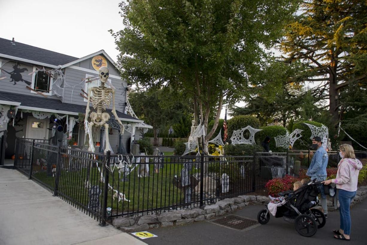 Alice and Lela Cummings, 3 and 5, and their parents, Dave and Meghaan, admire Jim and Ceci Mains' Halloween extravaganza in west Vancouver. This year the Mainses have built a 20-foot candy chute into their design in order to get sweets into kid's hands.