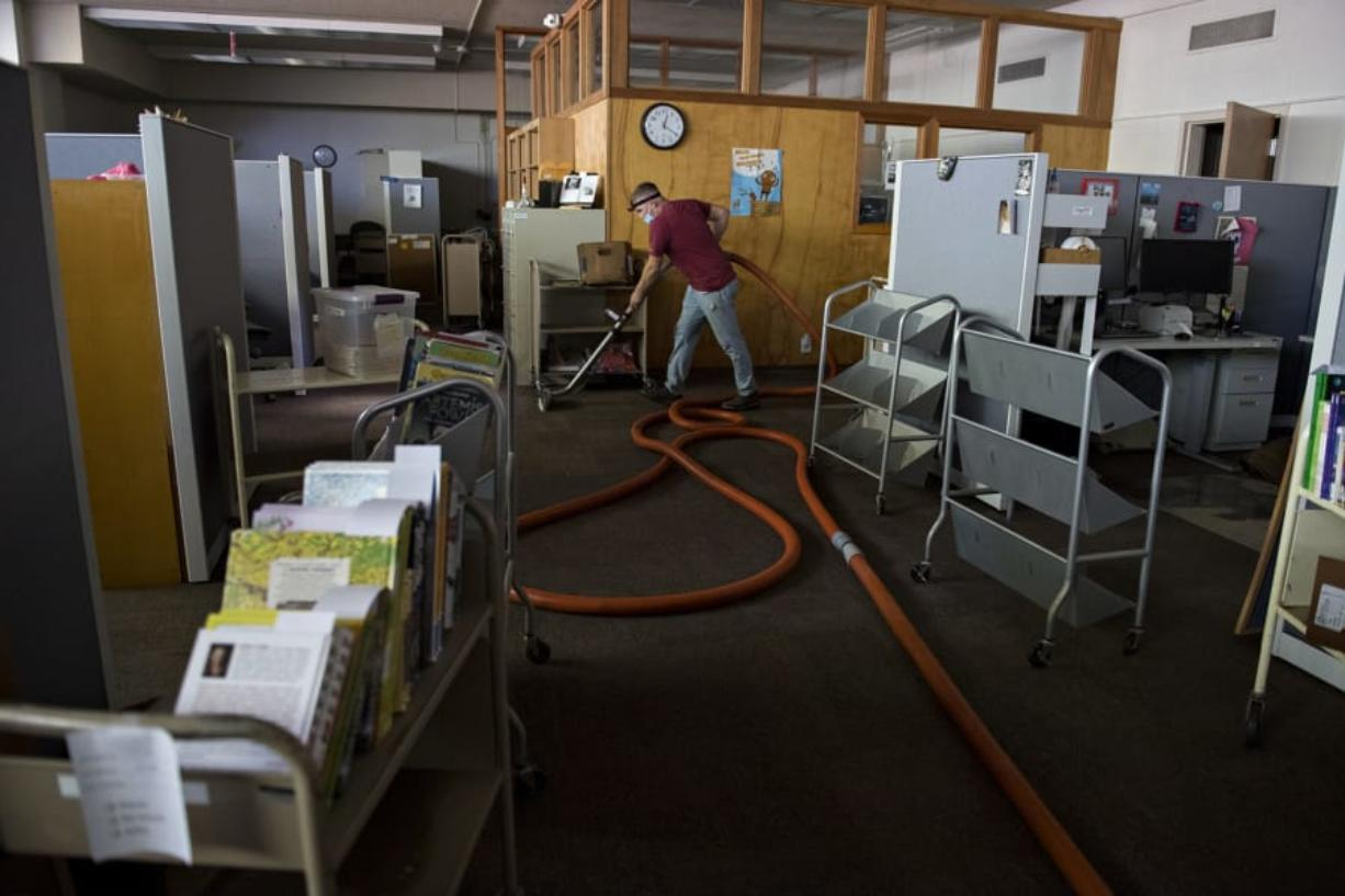 Trevor Burns of D&H Carpet Cleaning helps remove remaining water in the basement carpet and subfloor at Fort Vancouver Regional Library Operations Center on Monday afternoon. A ruptured water main flooded part of the facility over the weekend.