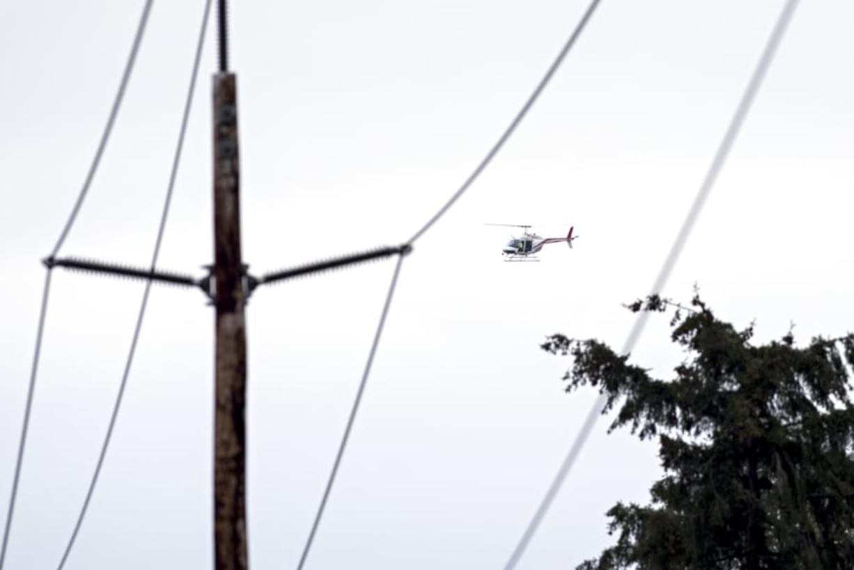 Clark Public Utilities staff ride in a helicopter to inspect vegetation around a transmission line in northwestern Camas. The utility provider is hoping that adding helicopter and drone flights will allow it to be more proactive in monitoring vegetation and making sure its power lines stay clear.