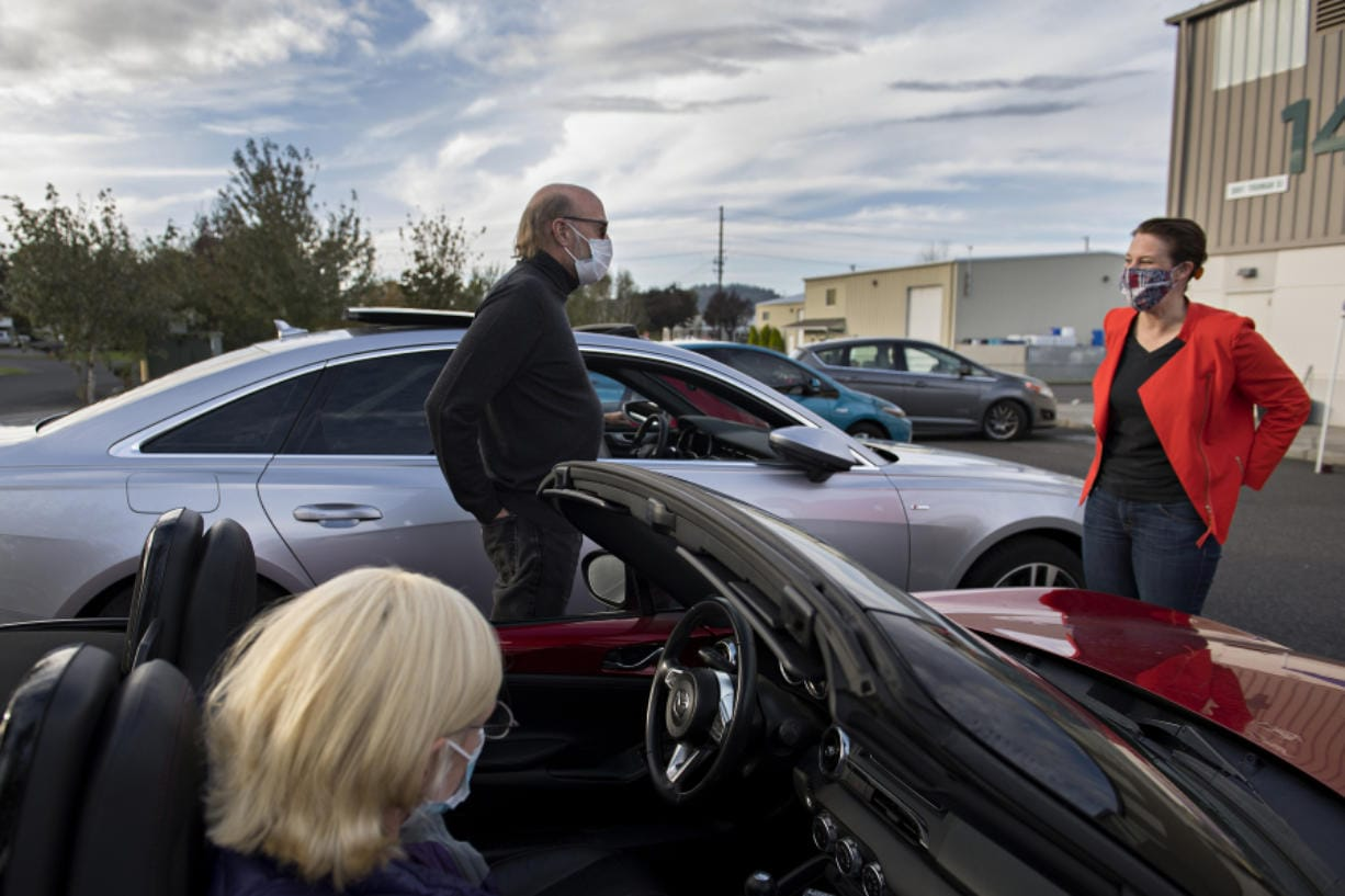 Jo Ellen Jarvis and Dave Watson wear masks while getting a few minutes to chat with congressional candidate Carolyn Long before a drive-in town hall in Washougal on Monday.