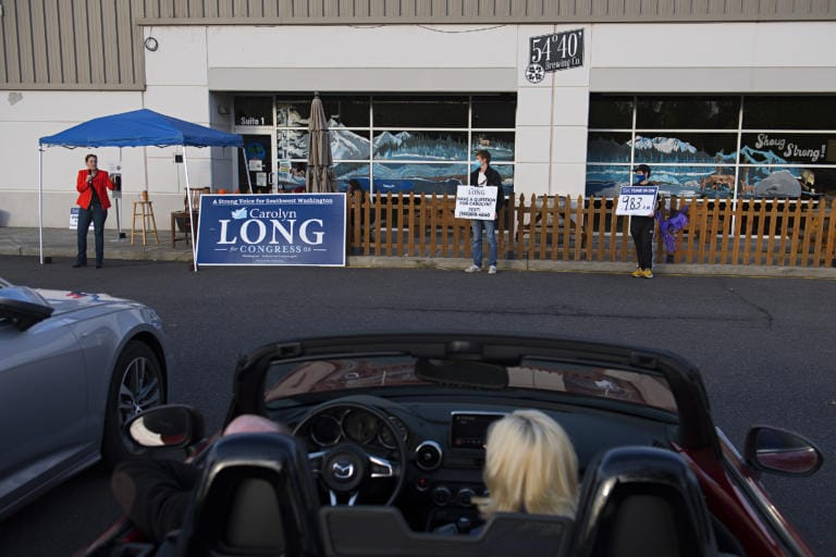 Congressional candidate Carolyn Long, from left, speaks to voters in Washougal during a drive-in town hall while joined by supporters Riley Coler and Joe-Henry McQuary on Monday evening, Oct. 12, 2020. (Amanda Cowan/The Columbian)