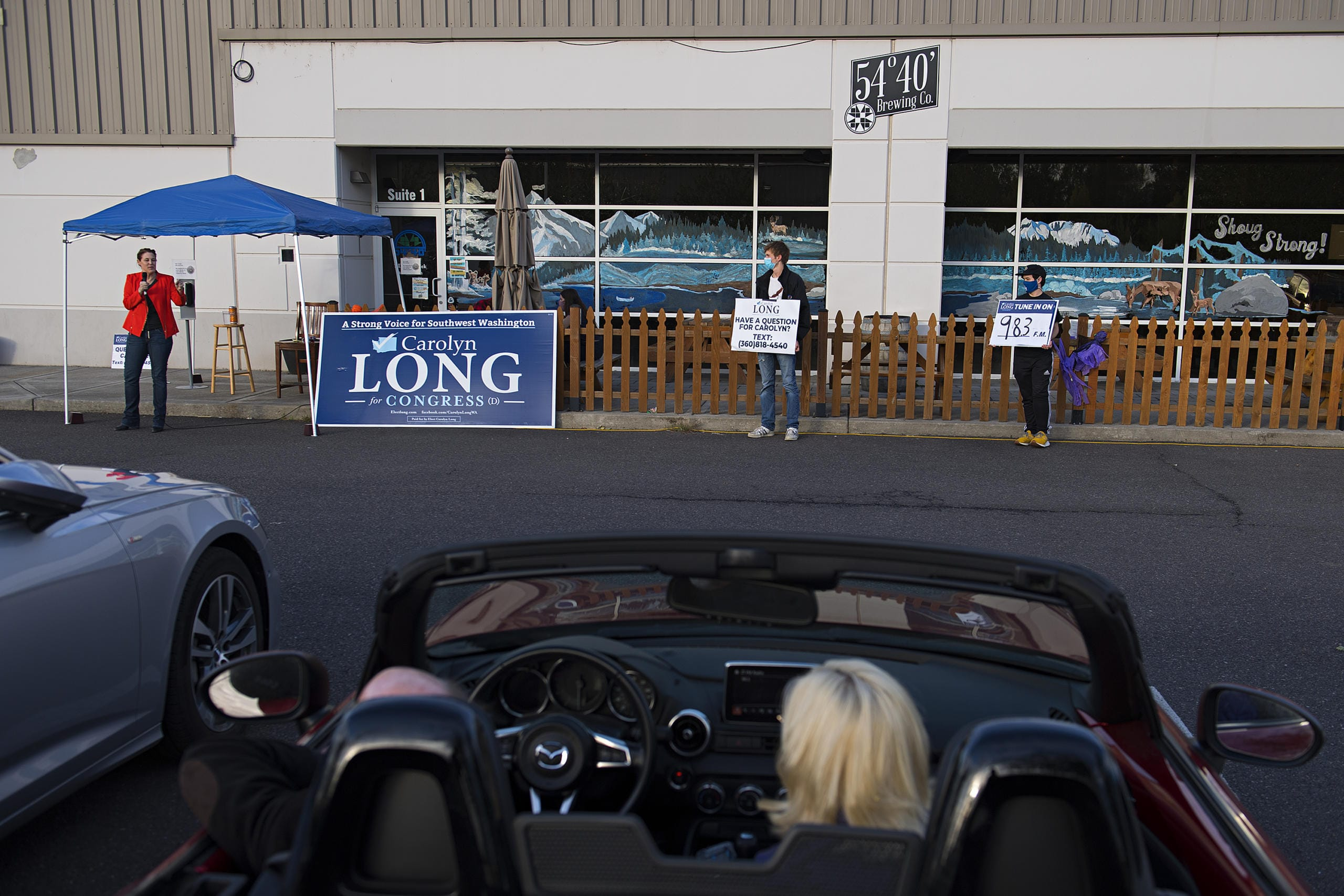 Congressional candidate Carolyn Long, from left, speaks to voters in Washougal during a drive-in town hall while joined by supporters Riley Coler and Joe-Henry McQuary on Monday evening, Oct. 12, 2020.