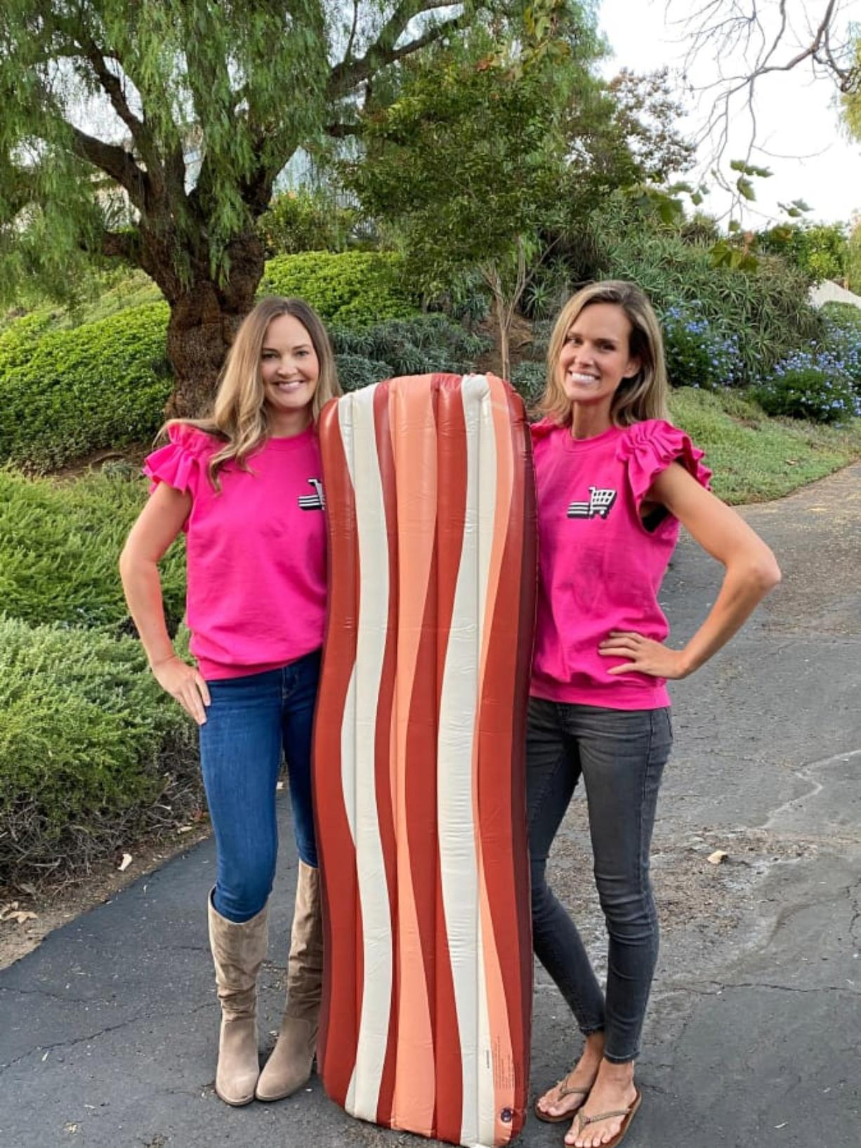 """Teammates Lois Arbogast and Julia Warren, a 2003 Skyview High School graduate, pose with a giant inflatable likeness of bacon. They compete on the reboot of """"Supermarket Sweep,"""" which premieres at 8 p.m. Sunday on ABC."""