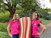 "Teammates Lois Arbogast and Julia Warren, a 2003 Skyview High School graduate, pose with a giant inflatable likeness of bacon. They compete on the reboot of ""Supermarket Sweep,"" which premieres at 8 p.m. Sunday on ABC."