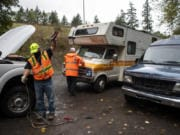 City workers help a woman jump-start her RV at Leverich Park in Vancouver on Tuesday. The city gave people staying at the park help with gasoline, jump-starts and offered them a tow to the Safe Park Zone at Evergreen Transit Center.