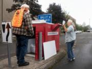 Vancouver resident Sharon Grammar, right, drops off her ballot while elections worker John Waterbury collects ballots from an official ballot drop box near the Clark County Elections Office in downtown Vancouver on Saturday morning.