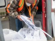 Elections worker John Waterbury collects ballots from an official ballot drop box Saturday in downtown Vancouver.