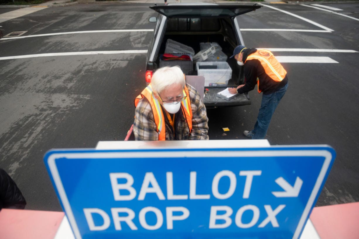 Elections workers John Waterbury, left, and Les Stark collect ballots from an official drop box near the Clark County Elections Office on Saturday morning, October 17, 2020.